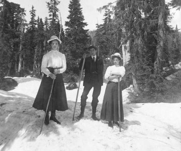 [Two women and a man holding walking sticks on snow]